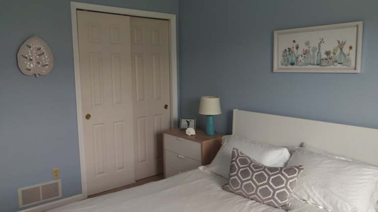 Bedroom with white bed and blue walls