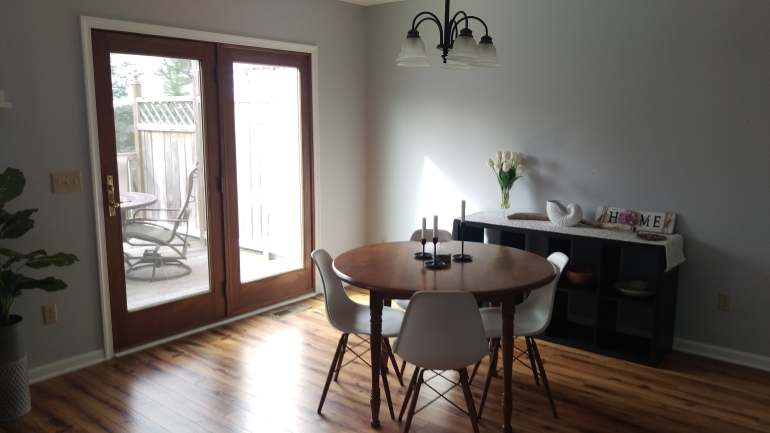 Wooden dining table with Eames chairs and black buffet in the background