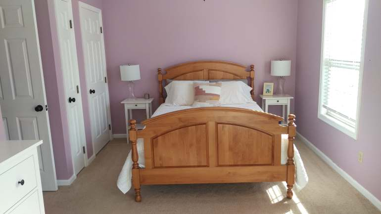 Bedroom with wooden bed and mauve walls