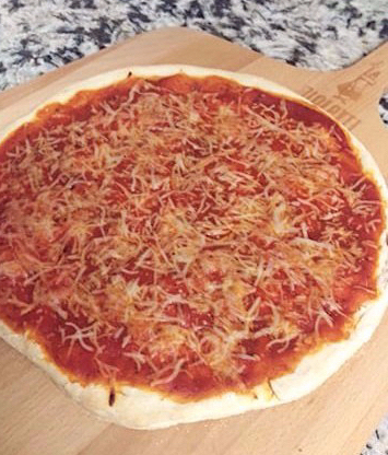Homemade cheese pizza on wooden pizza peel