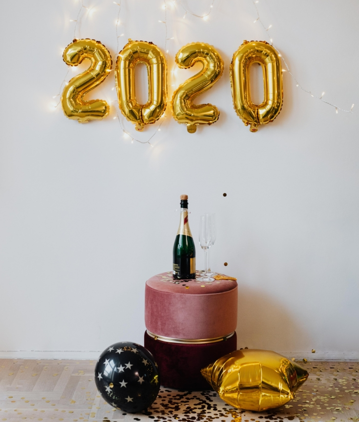 2020 number balloons attached to white wall with a pink ottoman holding a bottle of champagne