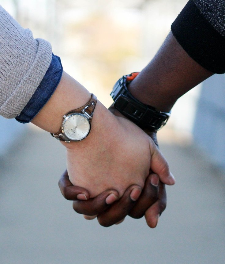 White person and black person holding hands